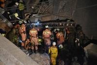 クレーン車でがれきを撤去した後、救助活動が続けられる16階ビルの倒壊現場=台湾台南市で2016年2月8日午後10時59分、鈴木玲子撮影