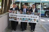 亡くなった大川小の児童たちの顔写真を並べた横断幕を掲げ、仙台地裁に入る遺族ら=仙台市青葉区で2016年10月26日午後1時半、喜屋武真之介撮影