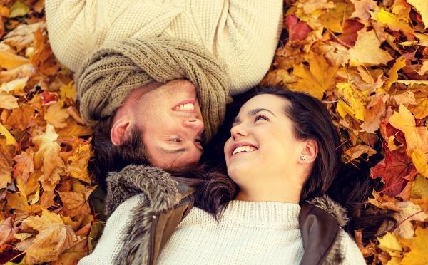 落ち葉の上で笑い合っている男女