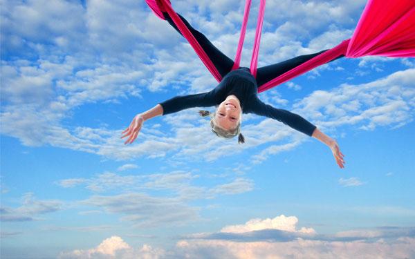空中でハンモックにつられている女性
