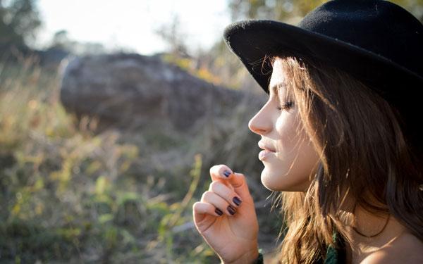 たそがれている黒い帽子をかぶった女性
