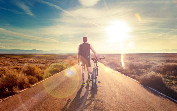草原の中にある一本道で自転車をひく男性