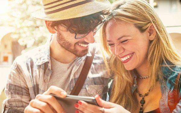 スマホを見ながら笑うカップル