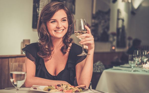 ワイングラスをもってほほ笑む女性