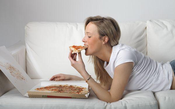 寝ころんでピザを食べる女性