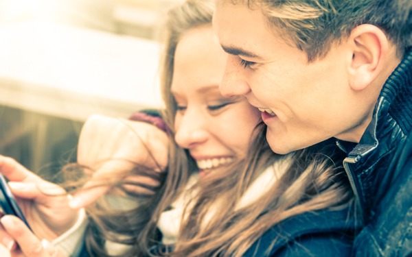 彼女のスマートフォンを見る、幸せそうなカップル