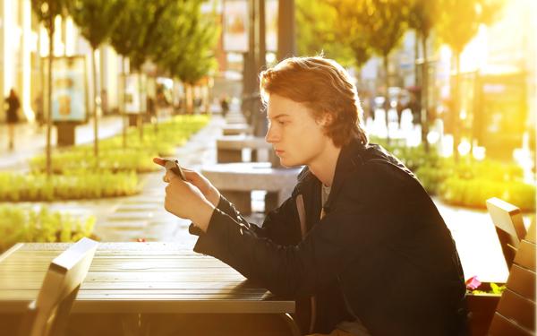 椅子に座ってスマートフォンをながめる男性