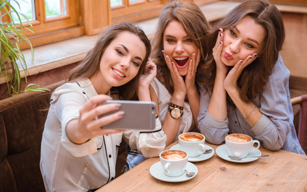 スマートフォンのカメラで、写真を撮っている三人の女性