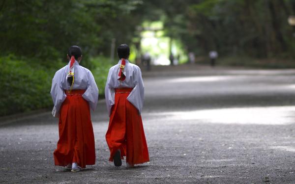 神社の境内を歩く二人の巫女