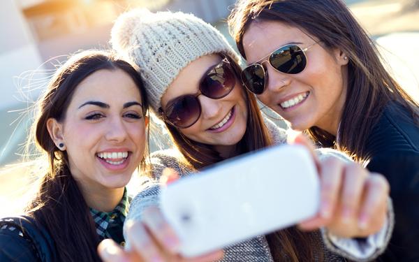 スマートフォンで写真を撮る仲良し女性3人組