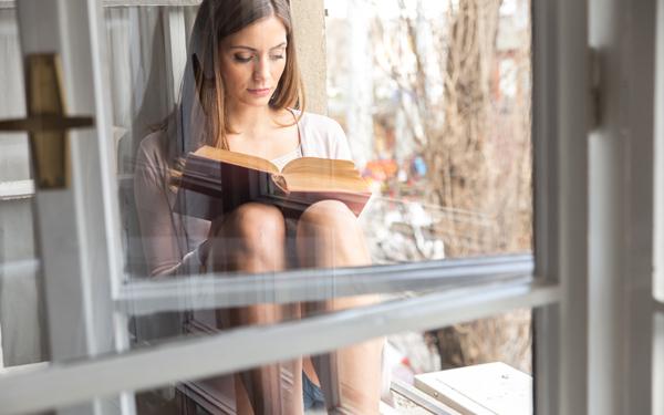 窓辺で本を読む女性