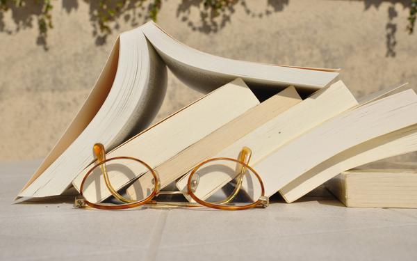 積み重なった本とメガネ