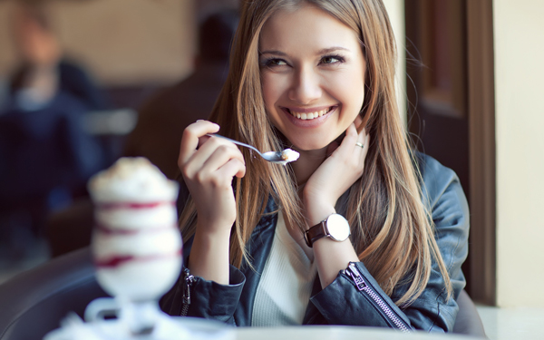 笑顔でデザートを食べる女性