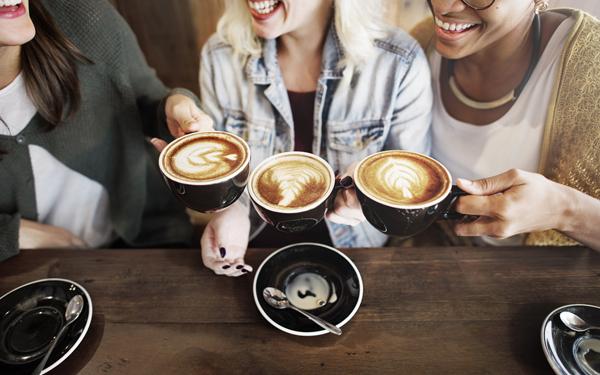 コーヒーを飲みながら談笑している3人の女性たち