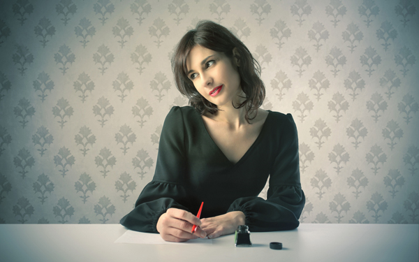 万年筆で手紙を書く女性