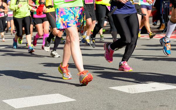 マラソン大会で歩道を走る女性ランナーたち