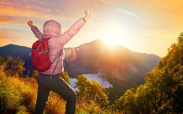 山頂からの日の出を見て喜ぶ女性