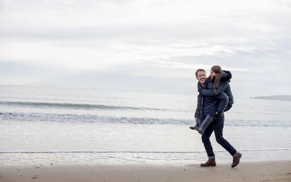 海辺で彼女をおんぶするカップ