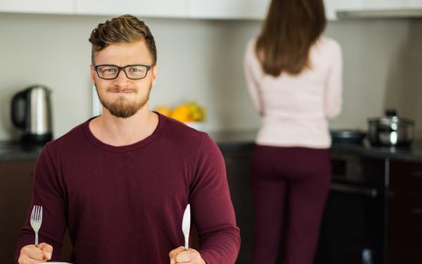 キッチンで食事を待つ男性