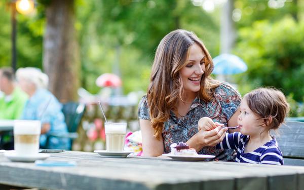 カフェで子供にケーキを食べさせてる母親