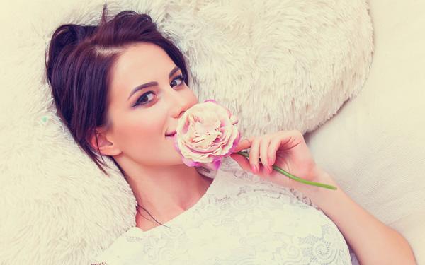 バラを口元にあてて微笑む女性