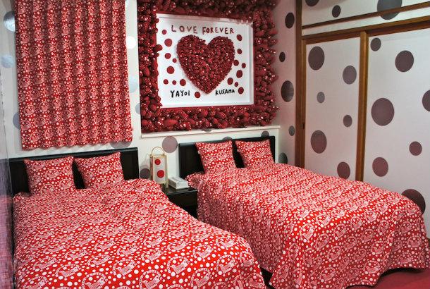ベッドの上には、ソフトスカルプチャーの新作「愛はとこしえ」を展示。壁からニョキニョキと\u201c生えて\u201dいるファブリック素材の突起物は、2013年、森美術館の「LOVE展」に
