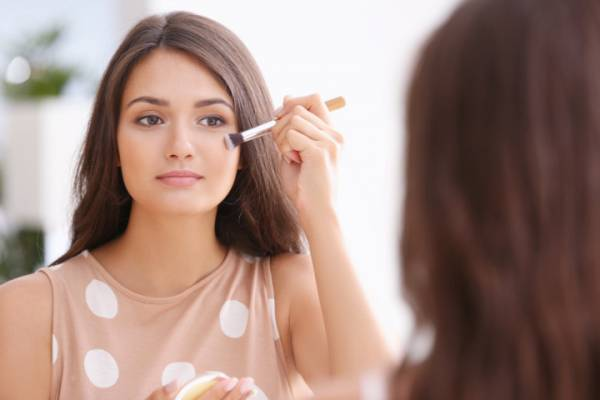 Beautiful girl applying cosmetics in front of mirror