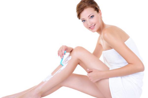 Caucasian woman shaving legs with razor
