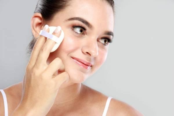 woman smiling while applying powder puff