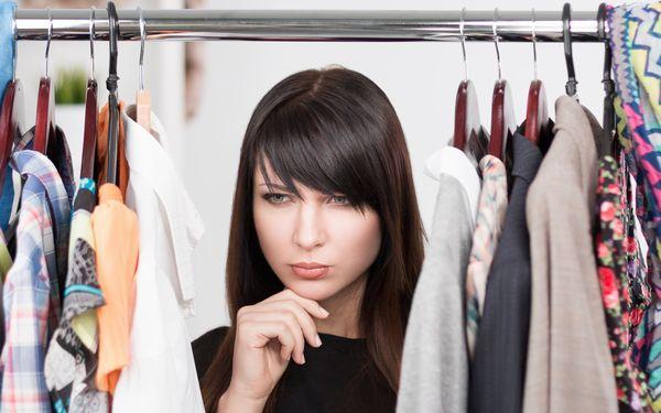 洋服の前で悩む女性