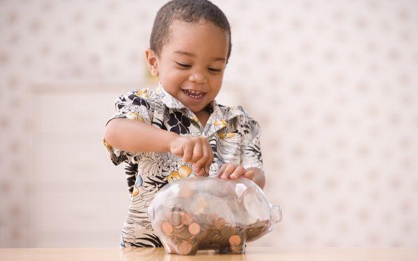 貯金箱にお金を入れる子ども