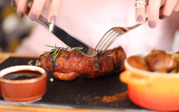 良く焼けた肉をナイフとフォークで切る女性