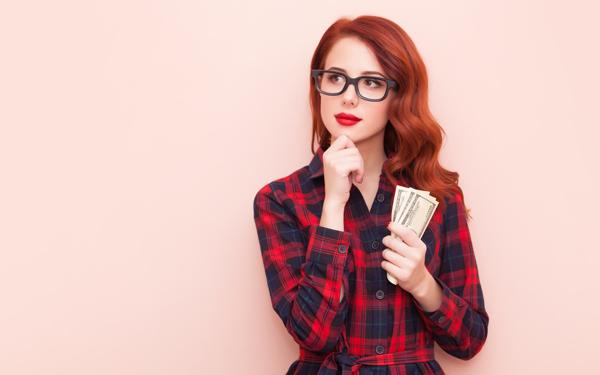 お金を握って考える女性