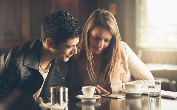 カフェでスマホを見る男女