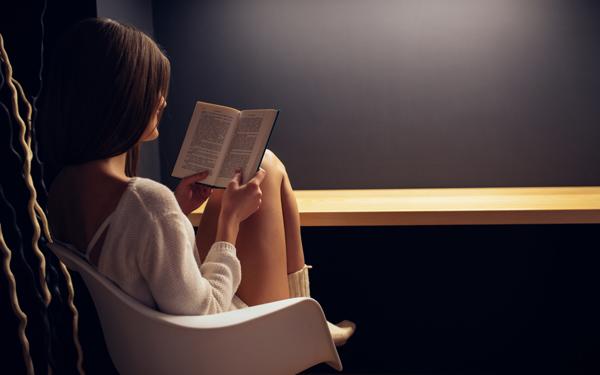 薄暗い部屋で、本を読んでいる女性