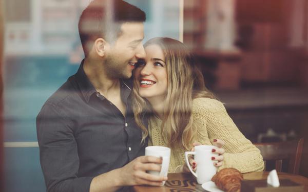 コーヒーショップで顔を寄せ合うカップル