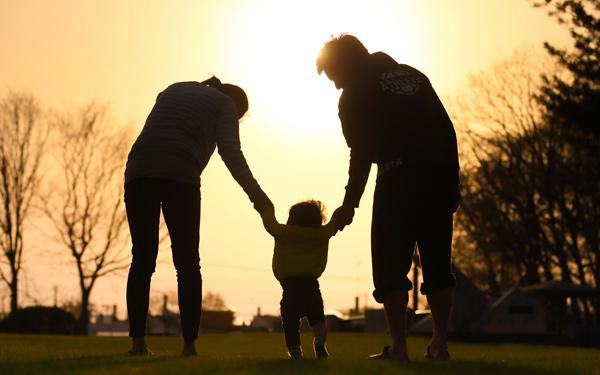 夕日を浴びた夫婦と子供