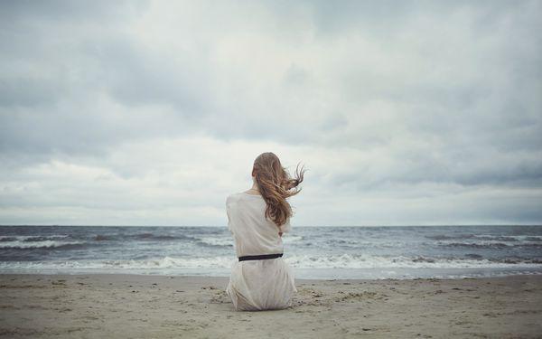 浜辺ですわる女性