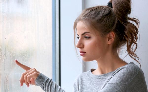雨の日の窓辺でもの思いにふける女性
