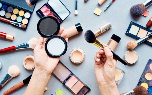 机の上に化粧品がならび、中央にブラシとパウダーを持つ手元が見える写真