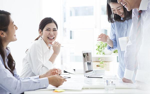 複数人で笑顔で話す女性