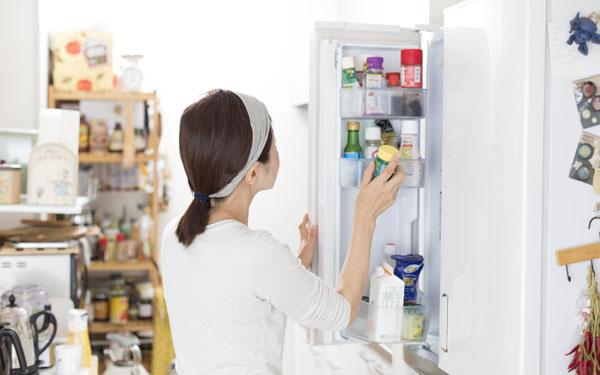 キッチンで冷蔵庫をあける女性