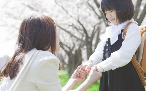 桜の下で手を取り合う親子