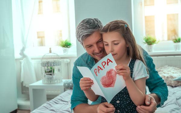 パパにカードを読む女の子