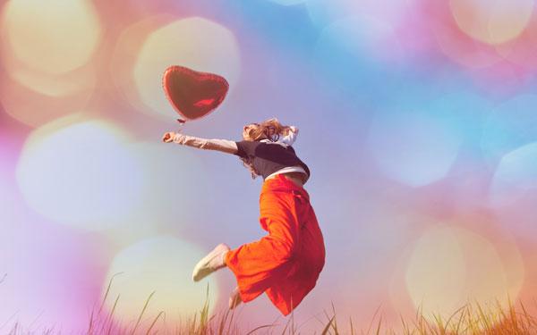 ハートの風船片手にジャンプしている女性