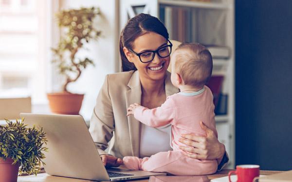 パソコンで仕事をしながら赤ちゃんの相手をするお母さん