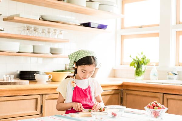 お菓子づくりのお手伝いが大好きなむすびちゃんが、苺を切るのを担当。ママの手作りエプロンもお似合いです。