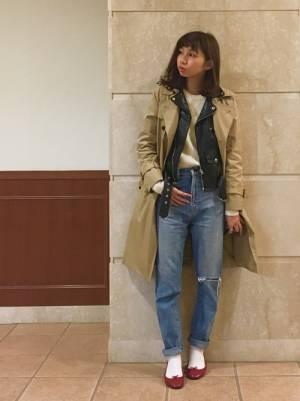 ライダースジャケットにトレンチコートを合わせてデニムを履いた女性