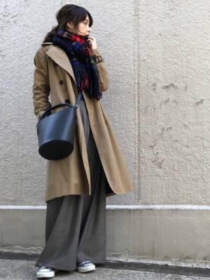 トレンチコートにグレンチェックのワイドパンツを合わせてチェックのストールを巻いた女性
