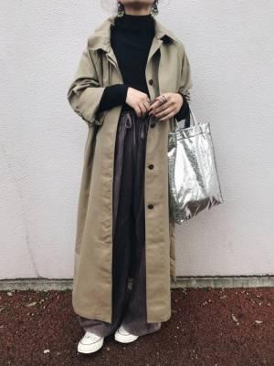 黒いトップスにコーデュロイのパンツを合わせてシルバーのバッグを持った女性